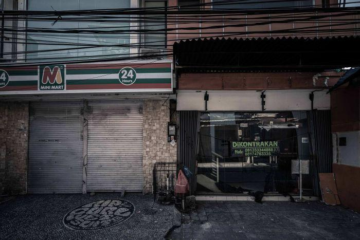Closed shopfronts in Kuta, Bali, with one up for lease.