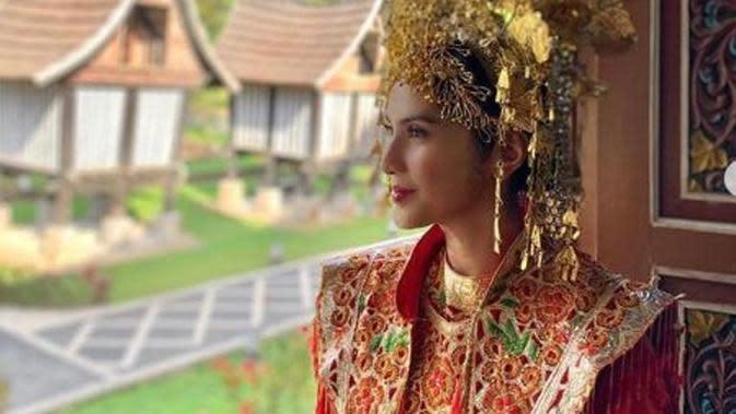 Maudy Koesnaedi memakai baju adat Minang dan suntiang di Rumah Gadang, Padang Panjang. (dok.Instagram @maudykoesnaedi/https://www.instagram.com/p/B3Y5RmzH7mx/Henry)
