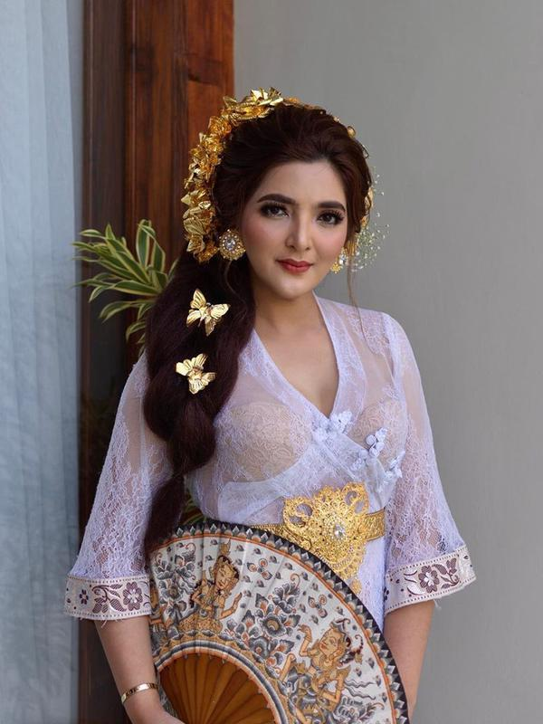 Nah, Ashanty juga cantik seperti perempuan Bali. Ia memakai kebaya putih dengan belt berwarna emas yang senada dengan hiasan di kepala dan antingnya. Anggun banget kan istri Anang Hermansyah ini? (Instagram/ashantyash)