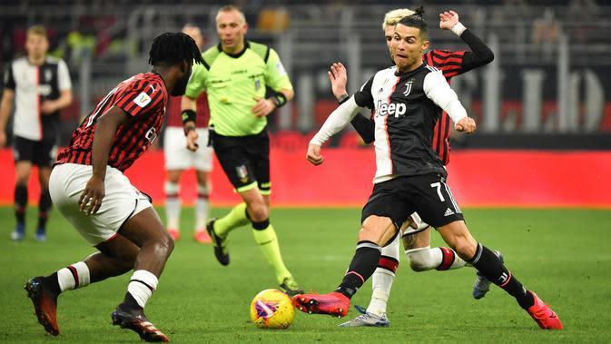 Pemain Juventus Cristiano Ronaldo (kanan) membawa bola mencoba melewati pemain AS Milan Frank Kessie pada pertandingan Coppa Italia di Stadion San Siro, Milan, Italia, Kamis (13/2/2020). Pertandingan berakhir 1-1. (Massimo Paolone/LaPresse via AP)