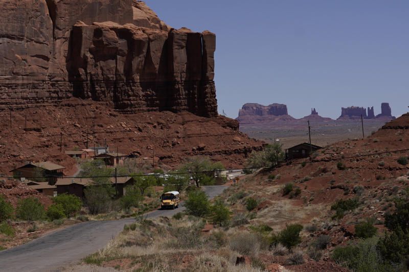 In this April 27, 2020, photo, a school bus is driven through Oljato-Monument Valley, Utah, on the Navajo reservation. Even before the pandemic, people living in rural communities and on reservations were among the toughest groups to count in the 2020 census. (AP Photo/Carolyn Kaster)