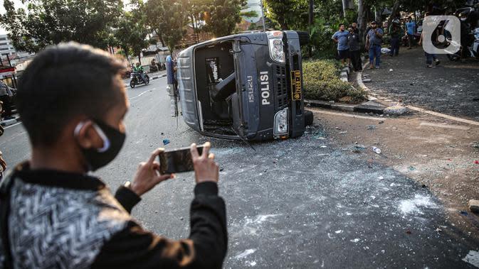 Seorang pria mengambil gambar sebuah mobil polisi yang dirusak massa saat bentrok di kawasan Pejompongan, Jakarta, Rabu (7/10/2020). (Liputan6.com/Faizal Fanani)