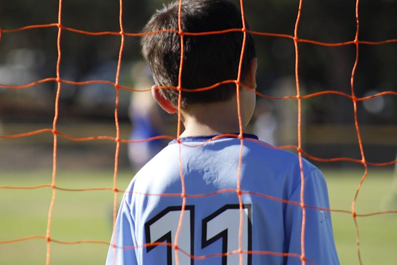 Rear View Of Boy Seen Though Chainlink Fence