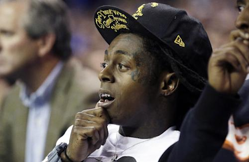 FILE - In this Nov. 13, 2012 file photo Entertainer Lil' Wayne attends the Duke-Kentucky NCAA college basketball game at the Georgia Dome in Atlanta. Lil Wayne says he's an epileptic and has had seizures for years. In an interview with Los Angeles-based radio station Power 106 on Thursday, March 28, 2013, the 30-year-old rapper said epilepsy caused his most recent health scare earlier this month, when he was rushed to a hospital. Wayne said he had three back-to-back seizures. (AP Photo/Dave Martin)