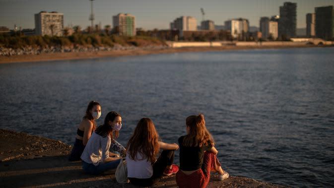 Sejumlah wanita mengenakan masker duduk di depan laut di Barcelona, Spanyol, Rabu, (20/5/2020). Berjemur dan berenang masih tidak diizinkan di pantai tersebut. (AP Photo/Emilio Morenatti)