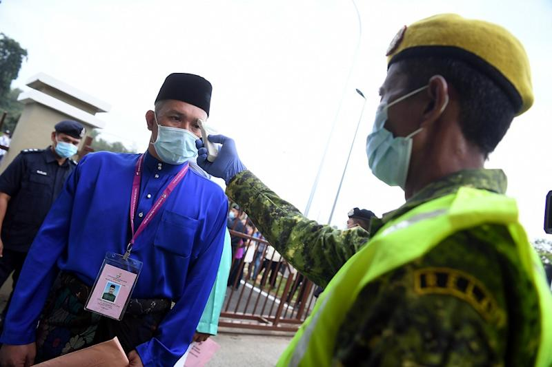 BN's Mohd Sharim Md Zain gets his temperature checked before entering the nomination centre in Pekan June 20, 2020. ― Bernama pic