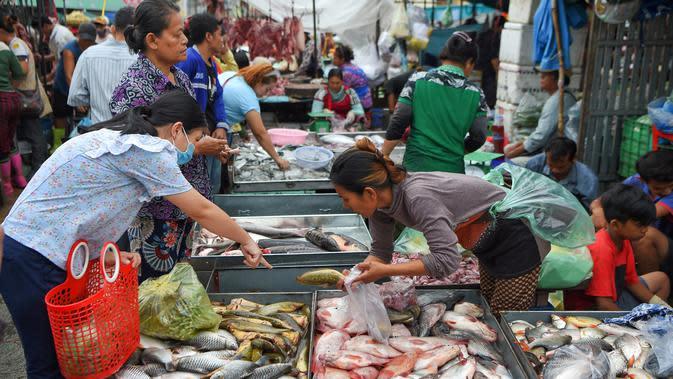 Seorang pelanggan memilih ikan dari penjual ikan di sebuah pasar di Phnom Penh (24/7/2020). Ibu kota Kamboja ini dipenuhi pasar baik besar maupun kecil. (AFP/Tang Chhin Sothy)