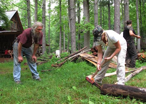Eustace Conway, left, offers encouragement as a camper hammers a wedge into a log at his Turtle Island Preserve in Triplett, N.C., on Thursday, June 27, 2013. People come from all over the world to learn natural living and how to go off-grid, but local officials ordered the place closed over health and safety concerns. (AP Photo/Allen Breed)