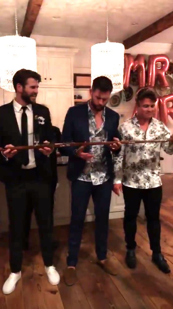 The Hemsworth brothers doing a shotski, with Mr. & Mrs. balloons in the background