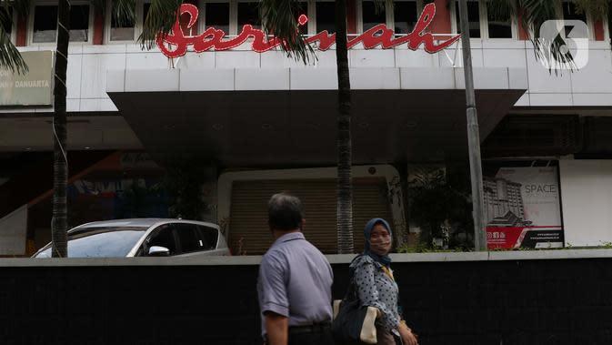 Warga berjalan di depan Gedung Sarinah, Jalan MH Thamrin, Jakarta, Selasa (12/5/2020). Pusat perbelanjaan pertama di Indonesia ini didirikan pada 17 Agustus 1962, dan resmi dibuka 15 Agustus 1966. Bangunan ini memiliki ketinggian sekitar 74 meter dengan 15 lantai. (Liputan6.com/Helmi Fithriansyah)