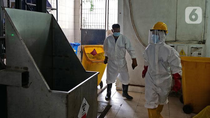 Petugas bersiap melakukan proses pembakaran limbah medis dalam incinerator di RSCM Jakarta, Jumat (26/6/2020). Menteri Lingkungan Hidup, Siti Nurbaya Bakar menyebutkan volume limbah medis infeksius di seluruh Indonesia hingga 8 Juni 2020 mencapai lebih dari 1.100 ton. (Liputan6.com/Herman Zakharia)