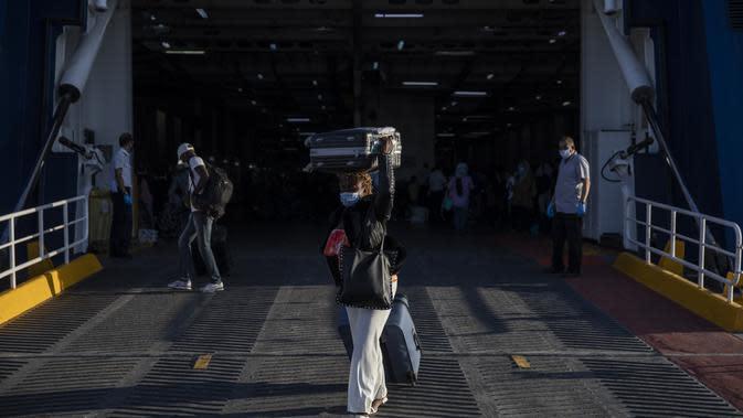 Pengungsi dan migran turun dari kapal feri di pelabuhan Lavrio, Athena (29/9/2020). Otoritas Yunani telah memindahkan hampir 1.000 pencari suaka dari pulau-pulau Aegean timur ke daratan sebagai bagian dari upaya untuk memperbaiki kondisi di kamp pulau yang penuh sesak.(AP Photo/Petros Giannakouris)