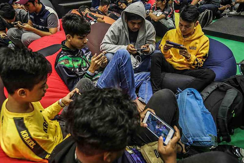 Children may have peers that play games at school and by disallowing them from participating, they may feel like an outcast. — Picture by Firdaus Latif