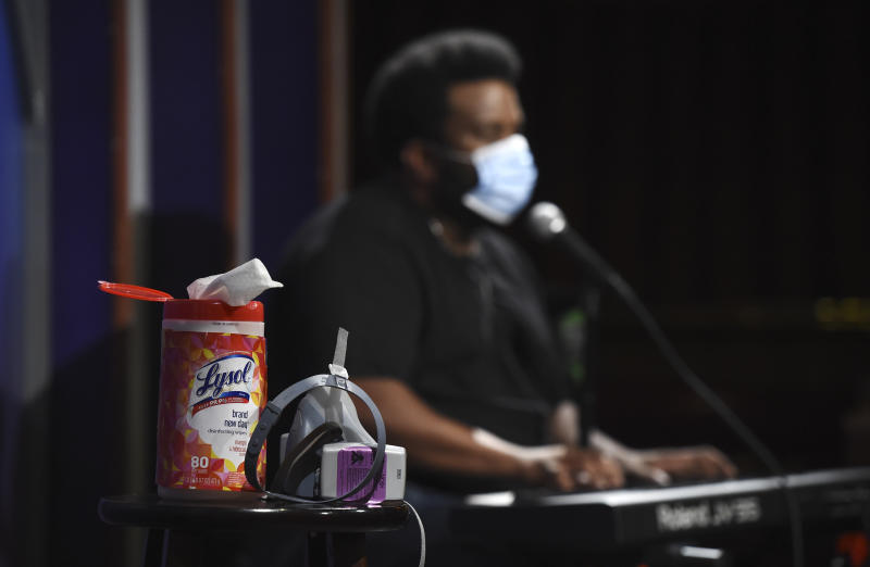 """In this April 20, 2020, photo, a bottle of Lysol disinfectant wipes sits on a table onstage as comedian Craig Robinson performs during a """"Laughter is Healing"""" stand-up comedy livestream event at the Laugh Factory in Los Angeles. With comedy clubs closed and concert tours put on hold, comics like Robinson, Tiffany Haddish, Will C  and others are keeping the jokes flowing on webcasts and Zoom calls even without the promise of a payday, because they say the laughs are needed now more than ever. (AP Photo/Chris Pizzello)"""