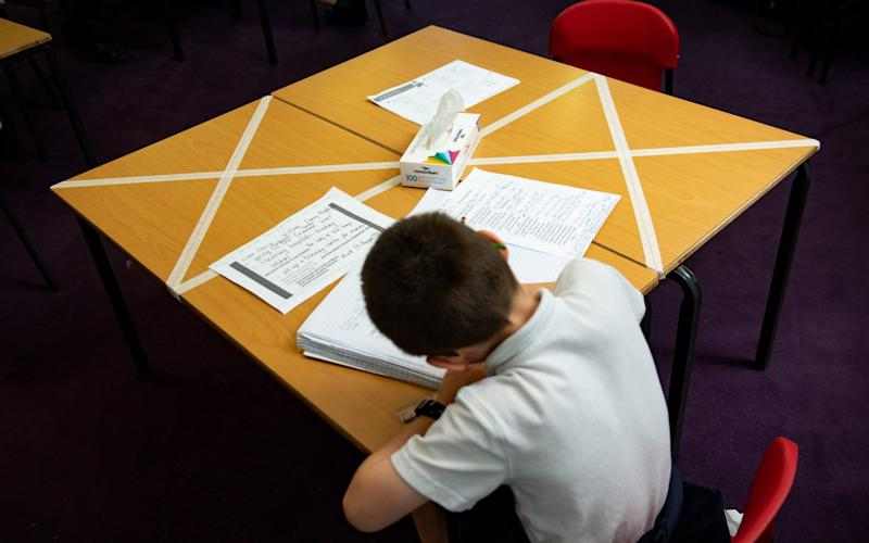 Social distancing measures as a child studies on a marked table at Kempsey Primary School in Worcester. - Jacob King/PA
