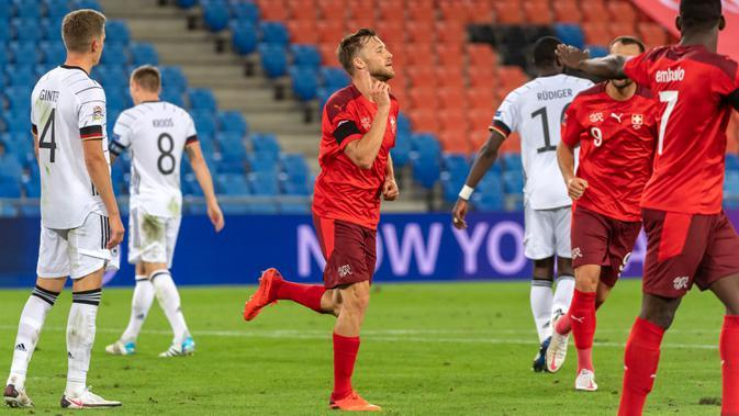 Bek Timnas Swiss, Silvan Widmer berselebrasi setelah mencetak gol ke gawang Timnas Jerman pada pertandingan kedua Liga A Grup 4 UEFA Nations League di St Jakob Park, Senin (7/9/2020) dini hari. Sementara itu Jerman dipaksa bermain imbang 1-1 oleh tuan rumah Swiss. (Georgios Kefalas/Keystone via AP)