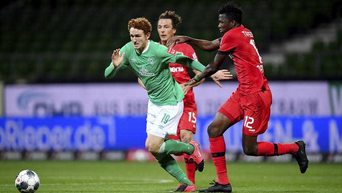 Pemain Bayer Leverkusen, Edmond Tapsoba, berebut bola dengan pemain Werder Bremen, Joshua Sargent, pada laga Bundesliga di Weserstadion, Bremen, Senin (18/5/2020). Bayer Leverkusen menang 4-1 atas Werder Bremen. (AP/Stuart Franklin)