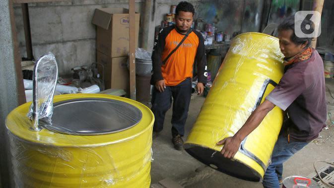 Perajin memproduksi wastafel portabel berbahan baku drum di workshop Galuh Creatives, Tangerang Selatan, Sabtu (30/5/2020). Wacana pemerintah menerapkan tatanan normal baru berimbas pada meningkatnya pesanan wastafel portabel yang dijual seharga Rp1,2 juta per unit. (merdeka.com/Arie Basuki)