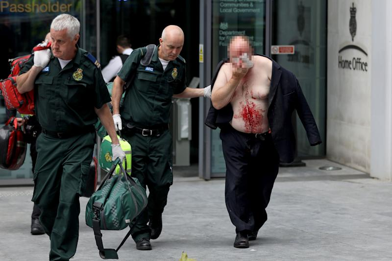 A man was pictured being led out of the Home Office covered in blood after running into the building for help. (Reuters)