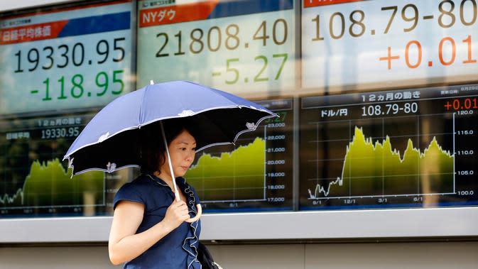 Seorang wanita berjalan melewati sebuah indikator saham elektronik sebuah perusahaan sekuritas di Tokyo (29/8). Akibat peluncuran rudal Korea Utara yang mendarat di perairan Pasifik saham Asia menglami penurunan. (AP Photo/Shizuo Kambayashi)