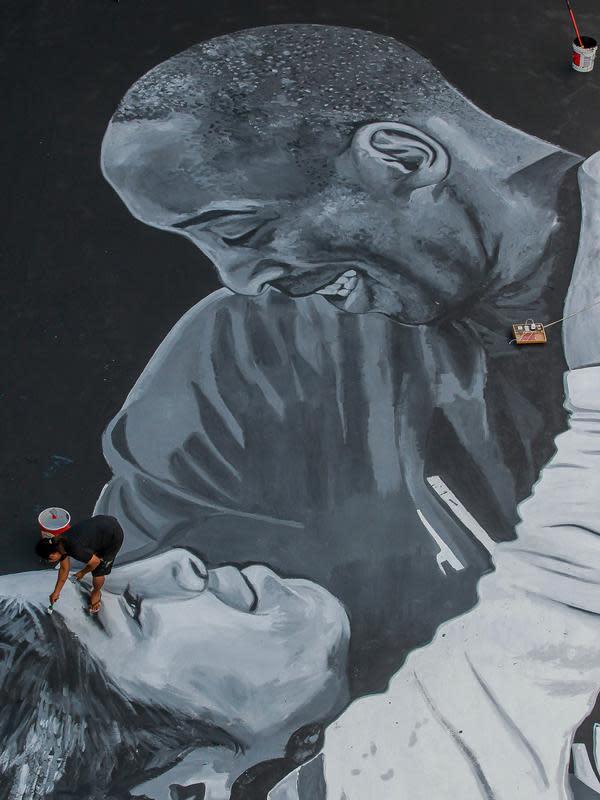 Seorang seniman melukis mural raksasa pada lantai sebuah lapangan basket untuk menghormati mantan bintang NBA Kobe Bryant dan putrinya Gianna di Taguig City, Filipina, Selasa (28/1/2020). Kobe Bryant dan Gianna meninggal dalam kecelakaan helikopter pada 26 Januari 2020. (Xinhua/Rouelle Umali)