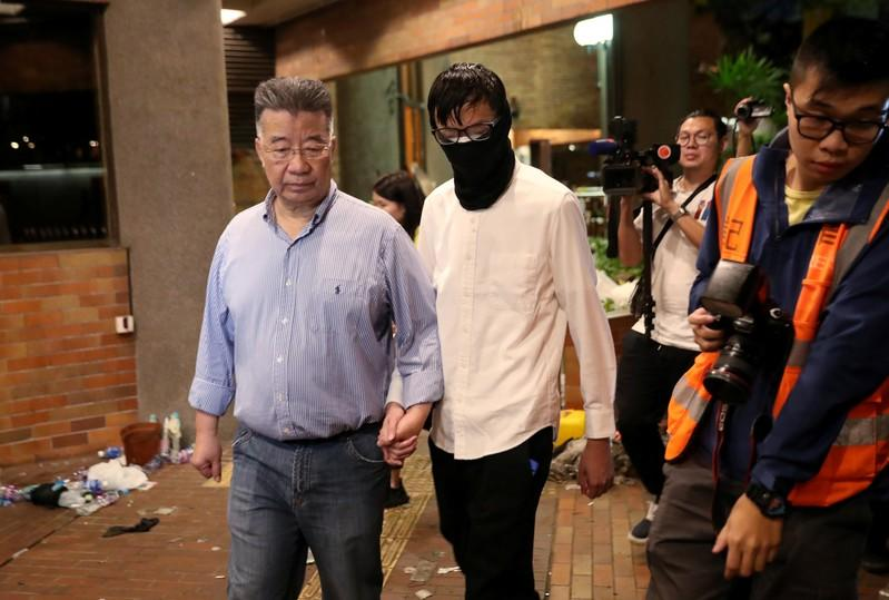 An anti-government protester is led out by Hong Kong businessman Lew Mon-hung, to give himself up to the police at Polytechnic University (PolyU) in Hong Kong