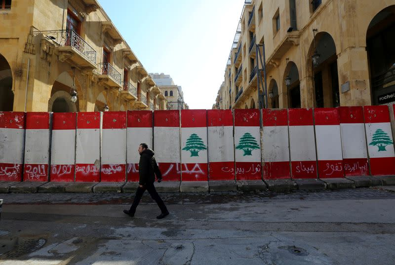 FILE PHOTO: A man walks past concrete barriers in Beirut