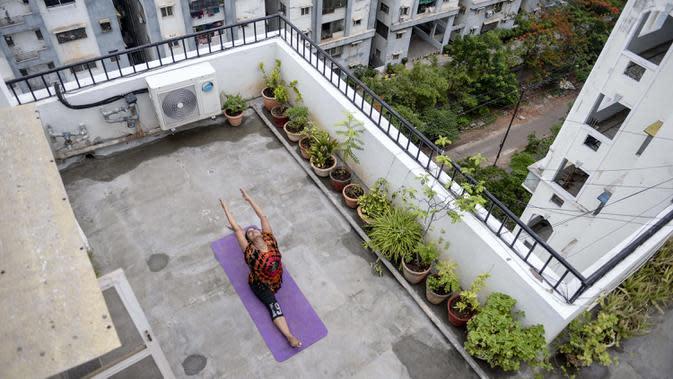 Instruktur yoga Pratibha Agarwal dari Anahata Yoga Zone melakukan gerakan yoga menjelang Hari Yoga Internasional di teras sebuah bangunan di Hyderabad, India pada 18 Juni 2020. Hari Yoga Internasional atau International Day of Yoga diperingati setiap tahun pada 21 Juni. (Photo by NOAH SEELAM / AFP)