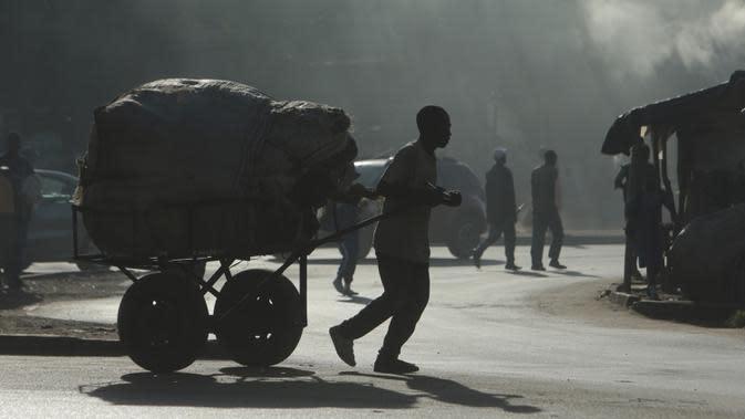 Seorang pria mengangkut muatan berat menggunakan gerobak di pinggiran kepadatan tinggi Mbare di Harare, Zimbabwe, Rabu (26/2/2020). Kota ini adalah pusat pemerintahan dan kota terbesar Zimbabwe, dengan perkiraan penduduk sebesar 1.606.000 (tahun 2009). (AP Photo/Tsvangirayi Mukwazhi)