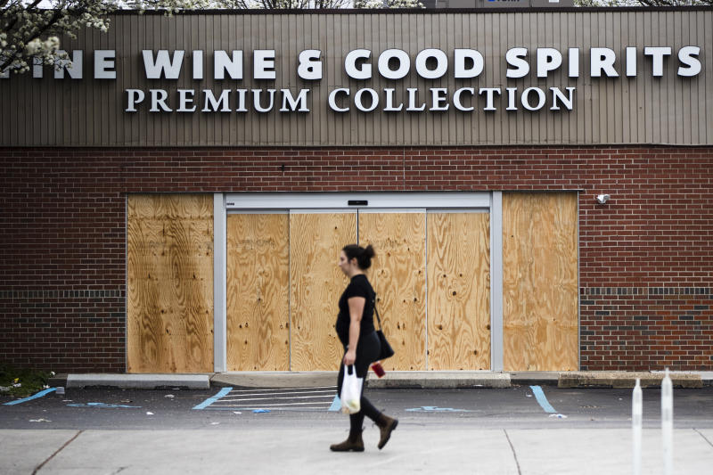 """A pedestrian walks past a boarded up Wine and Spirits store in Philadelphia, Friday, March 20, 2020. Pennsylvania Gov. Tom Wolf directed all """"non-life-sustaining"""" businesses to close their physical locations late Thursday and said state government would begin to enforce the edict starting early Saturday. (AP Photo/Matt Rourke)"""