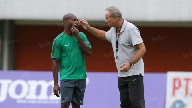 Alfred Riedl dan Boaz Solossa tengah berbincang saat sesi latihan di Stadion Maguwoharjo, Sleman, Jumat (07/10/2016). (Bola.com/Nicklas Hanoatubun)