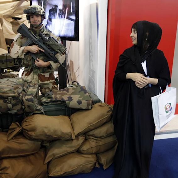 "An Emirati woman looks over at a French soldier during the launching of the International Defence Exhibition and Conference (IDEX) at the Abu Dhabi National Exhibition Centre in the Emirati capital on February 17, 2013. A top French defence industry official said that talks to sell Rafale jet fighters to the UAE were ""progressing well"", expressing confidence that a deal could be reached with the Gulf state."
