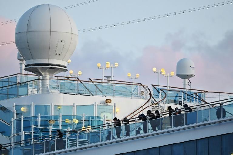 People still in quarantine stand on the deck of the Diamond Princess in Yokohama on February 18, 2020
