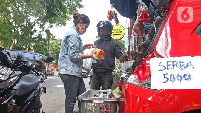 Cynthia (28) mahasiswi perguruan tinggi swasta (kiri) melayani calon pembeli di Jalan Santosa, Depok, Jawa Barat, Kamis (21/5/2020). Cynthia berjualan berbagai macam sayuran guna memenuhi kebutuhan sehari-hari di tengah pandemi Covid-19. (Liputan6.com/Herman Zakharia)