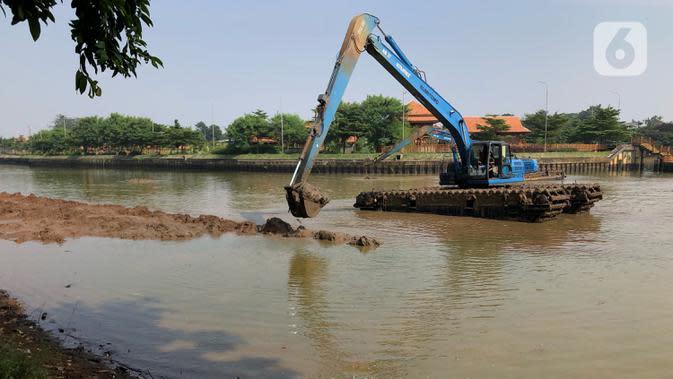 Petugas menggunakan alat berat untuk mengeruk lumpur di Setu Babakan, Jakarta, Selasa (30/6/2020). Pengerukan dilakukan guna mengembalikan kedalaman setu sehingga menambah daya tampungnya. (Liputan6.com/Immanuel Antonius)