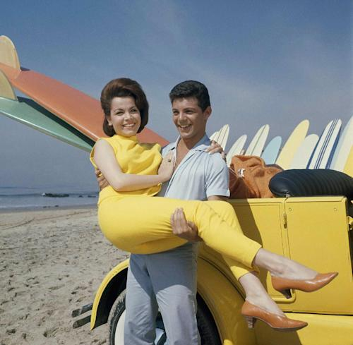 "FILE - In this 1963 file photo, singer Frankie Avalon and actress Annette Funicello are seen on Malibu Beach during filming of ""Beach Party,"" in California in 1963. Walt Disney Co. says, Monday, April 8, 2013, that former ""Mouseketeer"" Funicello, also known for her beach movies with Avalon, has died at age 70. (AP Photo/File)"