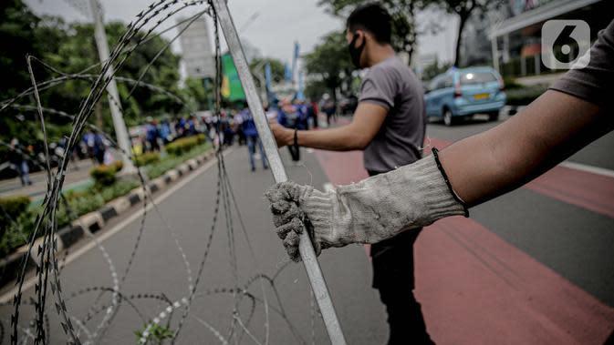 Personel kepolisian bersiap memasang kawat berduri untuk menjaga keamanan di sekitar Gedung DPR/MPR RI, Jakarta, Jumat (14/8/2020). Pengamanan ekstra itu untuk mengantisipasi rencana unjuk rasa menolak RUU Cipta Kerja yang bertepatan dengan Sidang Tahunan di Gedung DPR. (Liputan6.com/Faizal Fanani)