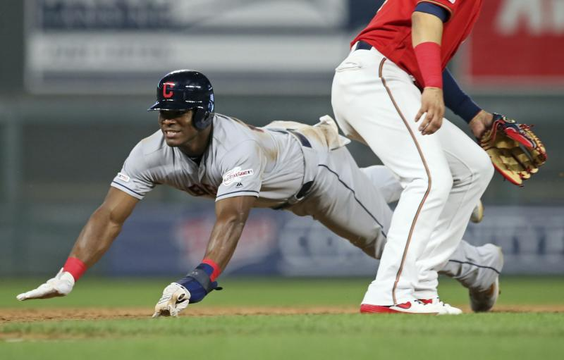 Cleveland Indians' Yasiel Puig, left, dives into third base, advancing from first after an error on a pickoff attempt at first in the ninth inning of a baseball game against the Minnesota Twins Friday, Aug. 9, 2019, in Minneapolis. The Indians won 6-2. (AP Photo/Jim Mone)