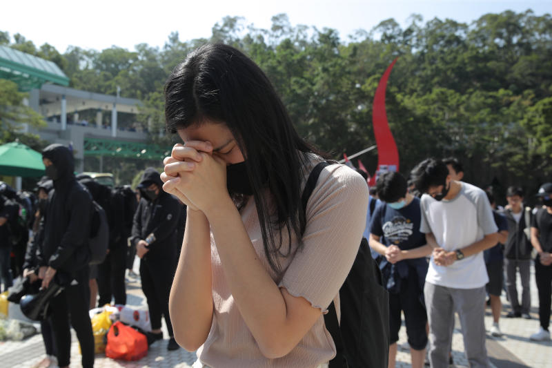 Protesters pause for a moment of silence after disrupting a graduation ceremony at the University of Science and Technology and turning the stage into a memorial venue for Chow Tsz-Lok in Hong Kong on Friday, Nov. 8, 2019. Chow, a student from the University who fell off a parking garage after police fired tear gas during clashes with anti-government protesters died Friday, in a rare fatality after five months of unrest that intensified anger in the semi-autonomous Chinese territory. (AP Photo/Kin Cheung)