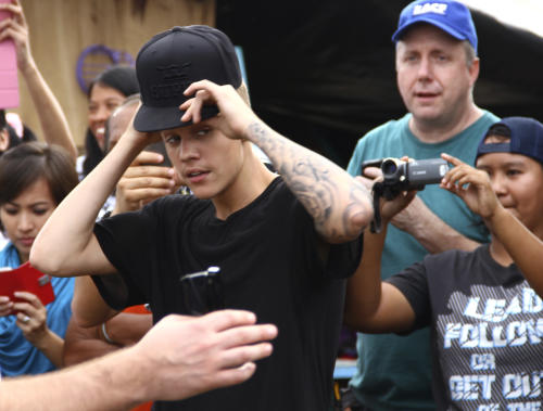 Justin Bieber adjusts his cap prior to playing basketball with children-survivors of Typhoon Haiyan during his visit to Tacloban city, Leyte province in central Philippines, Tuesday, Dec. 10, 2013. The teen heartthrob Bieber arrived Tuesday in the Philippines, where he has launched a campaign to help victims of last month's killer typhoon. (AP Photo)