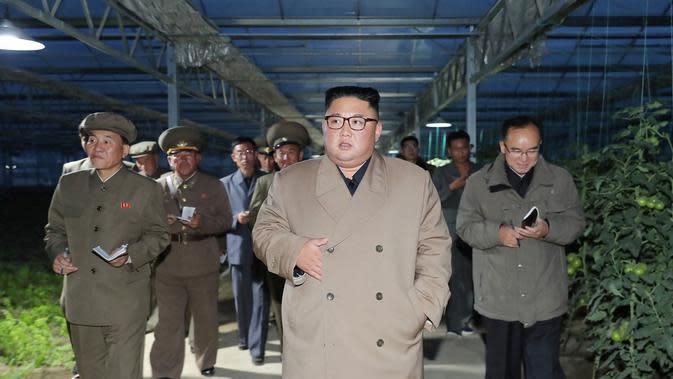 Pemimpin Korea Utara Kim Jong-un ditemani ajudannya saat mengunjungi Jungphyong Vegetable Greenhouse Farm and Tree Nursery yang sedang dibangun di Kyongsong, Korea Utara, Jumat (18/10/2019). Kunjungan tersebut untuk memastikan pasokan makanan stabil. (KCNA VIA KNS/AFP)