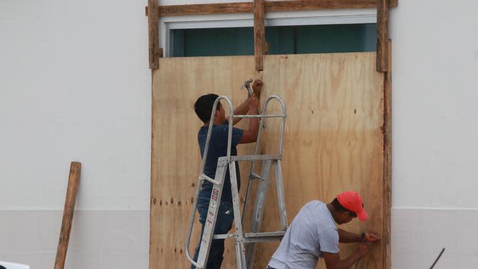 Para pekerja melapisi jendela dengan papan saat Badai Delta mendekati Puerto Morelos, Negara Bagian Quintana Roo, Meksiko, 6 Oktober 2020. Badai Delta diperkirakan akan melanda Negara Bagian Quintana Roo dengan hujan lebat, angin kencang, dan gelombang setinggi 10 meter. (Xinhua/Israel Rosas)