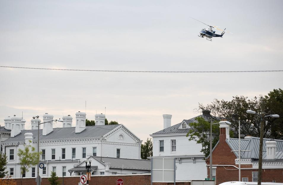 A police helicopter flies over the Washington Navy Yard as police respond to a shooting, in Washington