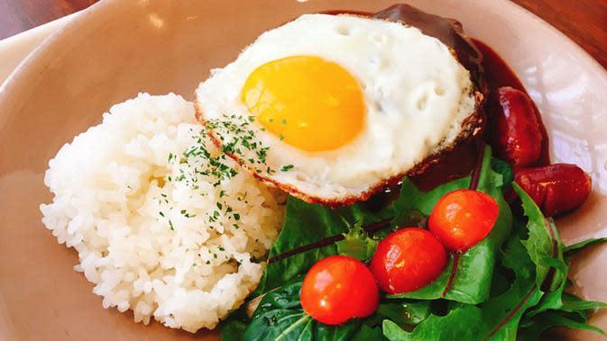Ilustrasi telur ceplok disajikan dengan nasi hangat.