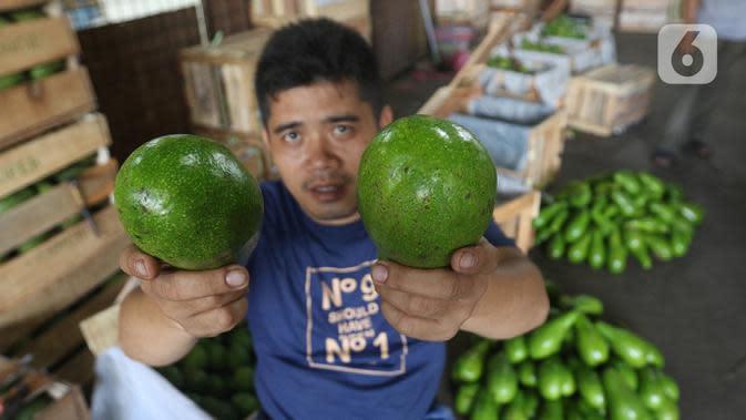 Pedagang menunjukkan buah alpukat di pasar induk Kramat Jati, blok buah di Jakarta, Minggu (2/2/2020). Pemerintah berupaya melakukan peningkatan produksi buah-buahan dalam negeri dan diharapkan tidak hanya dilakukan untuk mendongkrak ekspor. (Liputan6.com/Herman Zakharia)