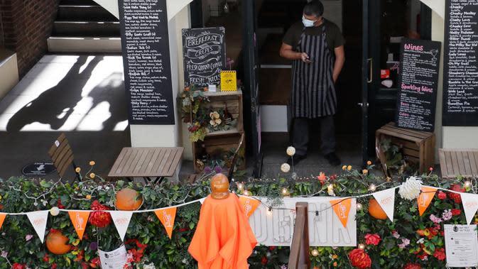 Pramusaji menunggu pelanggan di sebuah kafe outdoor di London setelah PM Inggris Boris Johnson mengumumkan serangkaian pembatasan baru, Kamis (24/9/2020). PM Boris meminta warga Inggris mengikuti aturan pembatasan sosial baru yang akan berlangsung selama enam bulan. (AP Photo/Kirsty Wigglesworth)