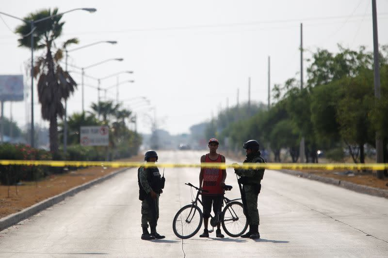 FILE PHOTO: Soldiers talks to a man at a crime scene after unknown assailants attacked a workshop leaving several casualties, according to local media, in Celaya