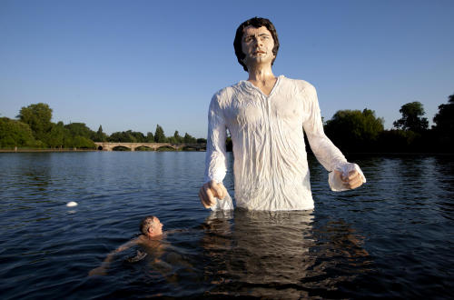 "A swimmer approaches a statue meant to depict actor Colin Firth performing as Mr. Darcy, a character in Jane Austen's novel ""Pride and Prejudice"" at the Serpentine Lake, Hyde Park, London, Monday, July 8, 2013. (AP Photo/PA, David Parry) UNITED KINGDOM OUT, NO SALES, NO ARCHIVE"