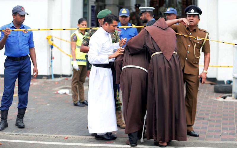 Priests walk into the St Anthony's Shrine, Kochchikade church after the explosion. Source: Reuters