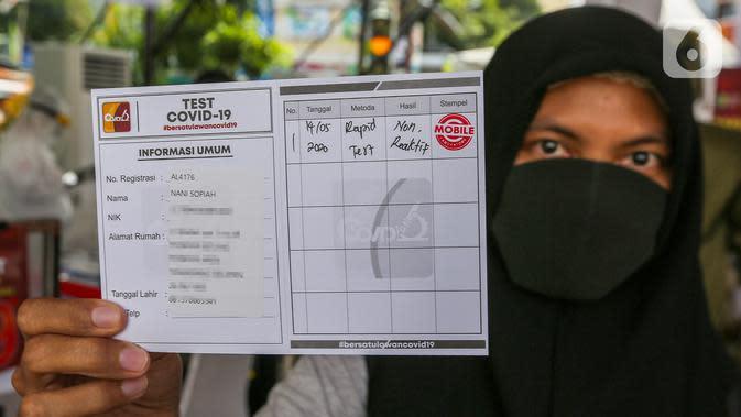 Warga menunjukkan kartu test Covid-19 usai rapid test massal di Kantor Kelurahan Pondok Betung, Tangerang Selatan, Kamis (14/5/2020). Rapid test yang digelar Badan Intelijen Negara (BIN) untuk memastikan positif atau tidaknya warga terjangkit Covid-19. (Liputan6.com/Fery Pradolo)